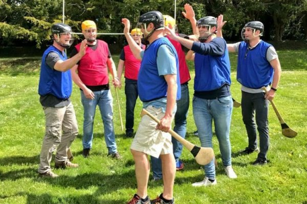 Team members congratulating each other & holding hurls during their team bonding hurling workshop with Orangeworks.