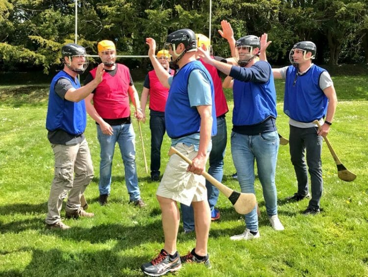 Team members congratulating each other & holding hurls during their team bonding hurling workshop with Orangeworks.