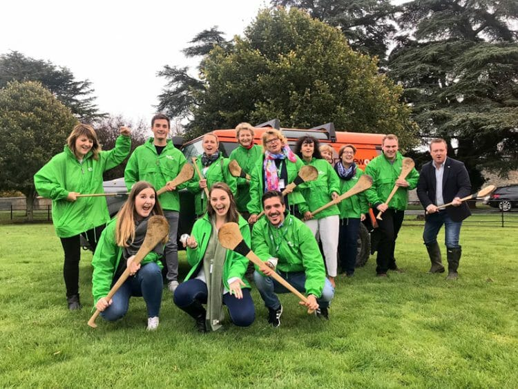 Delegates posing with their hurleys in hand as they finished the team building hurling worksho with orangeworks.