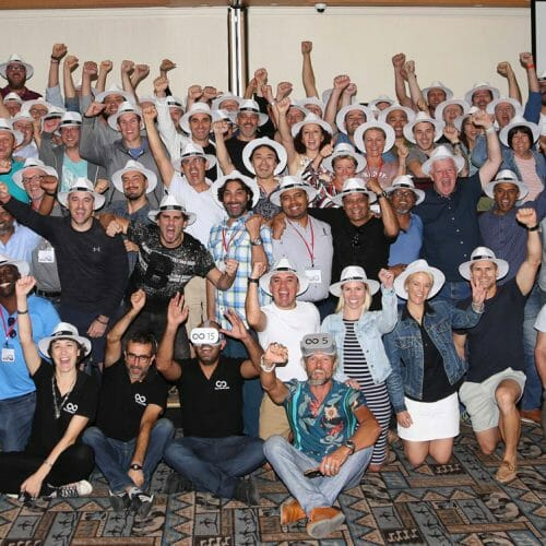 A group of delegates wearing white hats and posing for a photo when they finished Orangeworks virtual reality team activity.