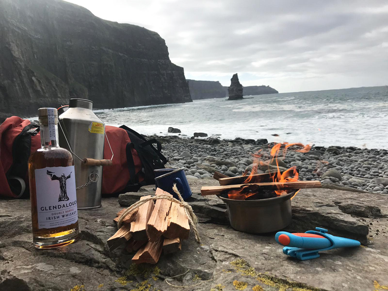 Whiskey, a kelly kettle & other utensils laid out to make hot whiskeys at the cliffs of Moher during orangeworks activities.