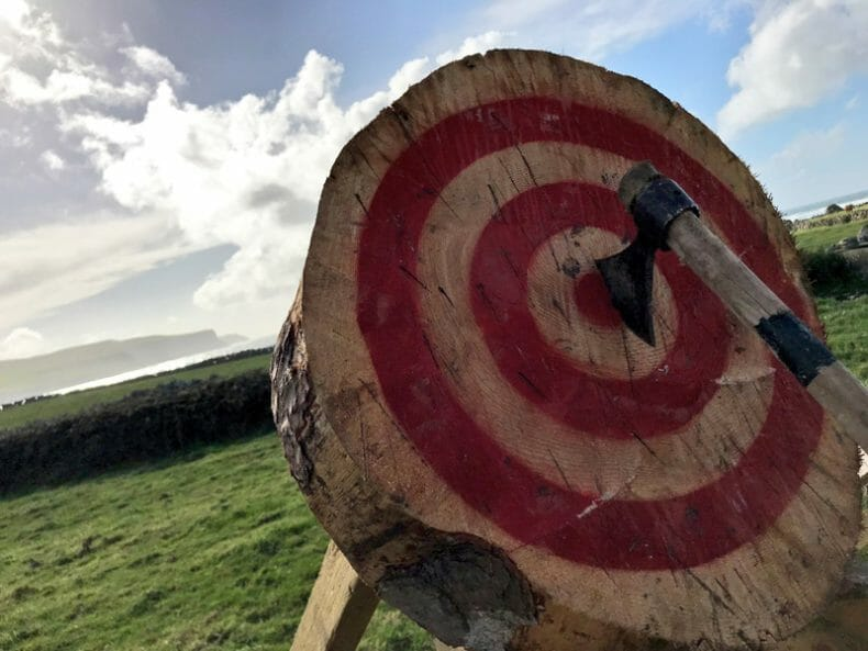 An axe on a target. Axe throwing is a team building activity organised by Orangeworks.