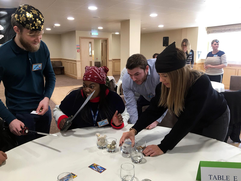 Delegates engaging with each other while participating in the pirate-themed negotiation game Trade Winds by Orangeworks.