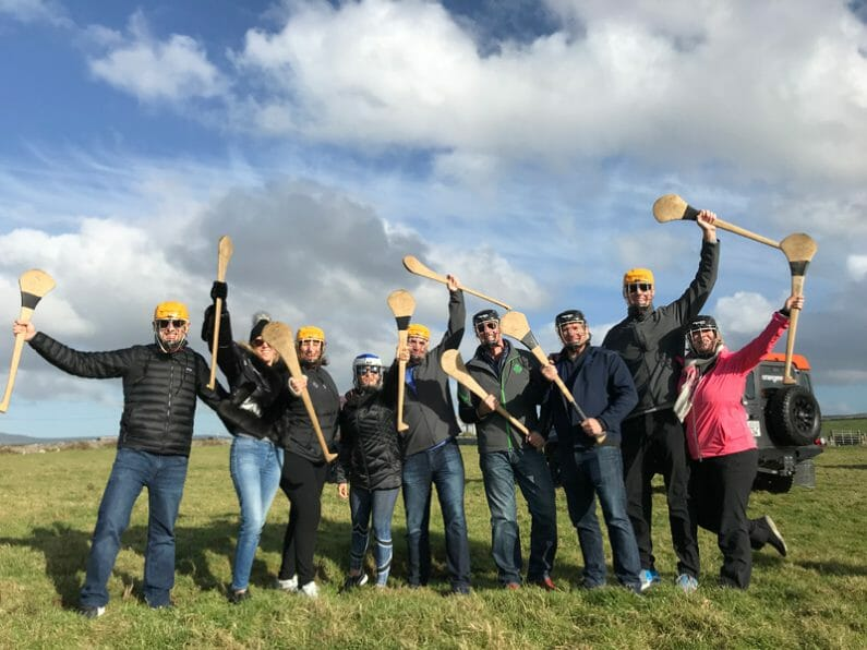 Delegates wearing helmets and holding hurls during their Hurling workshop, an engaging team building activity by Orangeworks.
