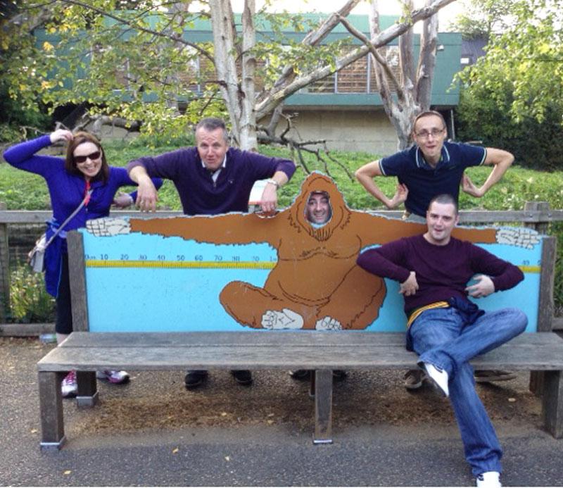 A group posing like monkeys at the Dublin Zoo during Orangeworks treasure hunt game called Go Team.