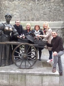 A group of people posing with the Molly Malone statue in Dublin's O Connell Street, during Orangeworks team building treasure hunt called Go Team Dublin.