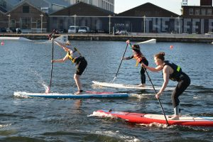 3 ladies paddle boarding duriung their team away day with surfdock watersports.