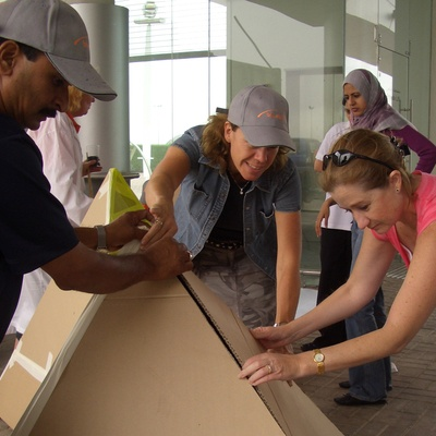 Delegates of flat out pyramids by orangeworks, working together to align the cardboard into pyramid shape.