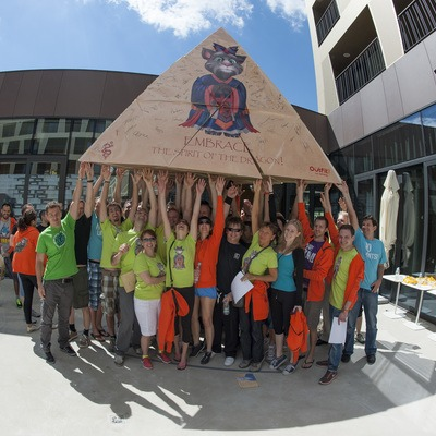 A team holding up a giant cardboard pyramid they made together during a team building exercise called flat out pyramids.