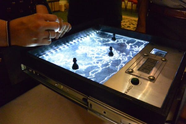 the red alert map game in a metal box with lights going through it, and a delegates hands on it.