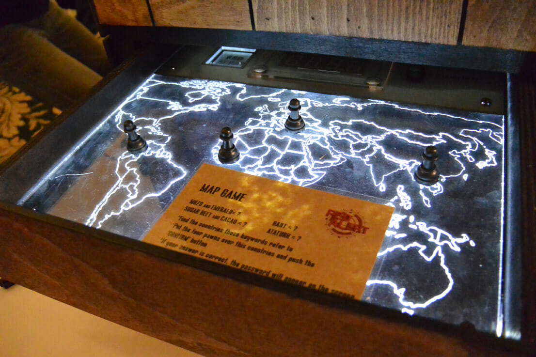 The red alert map game in a wooden box with lights going through it. Counters and instructions are placed on top.