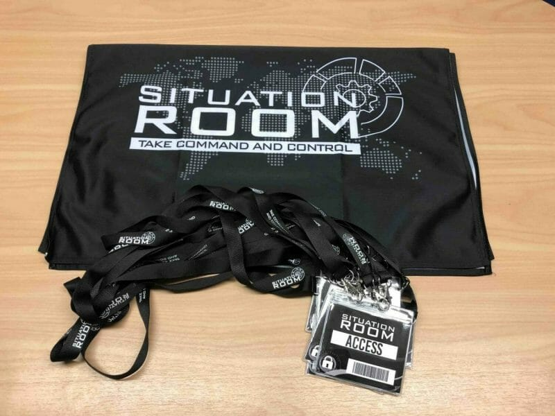 situation room bag laid out on a table with lanyards beside it.
