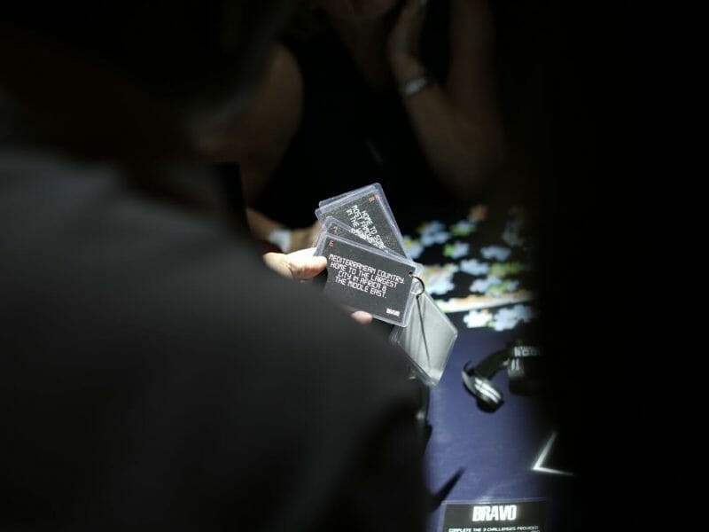 a zoomed in photo of someone holding cards in the situation room. A few things on the table in the background.