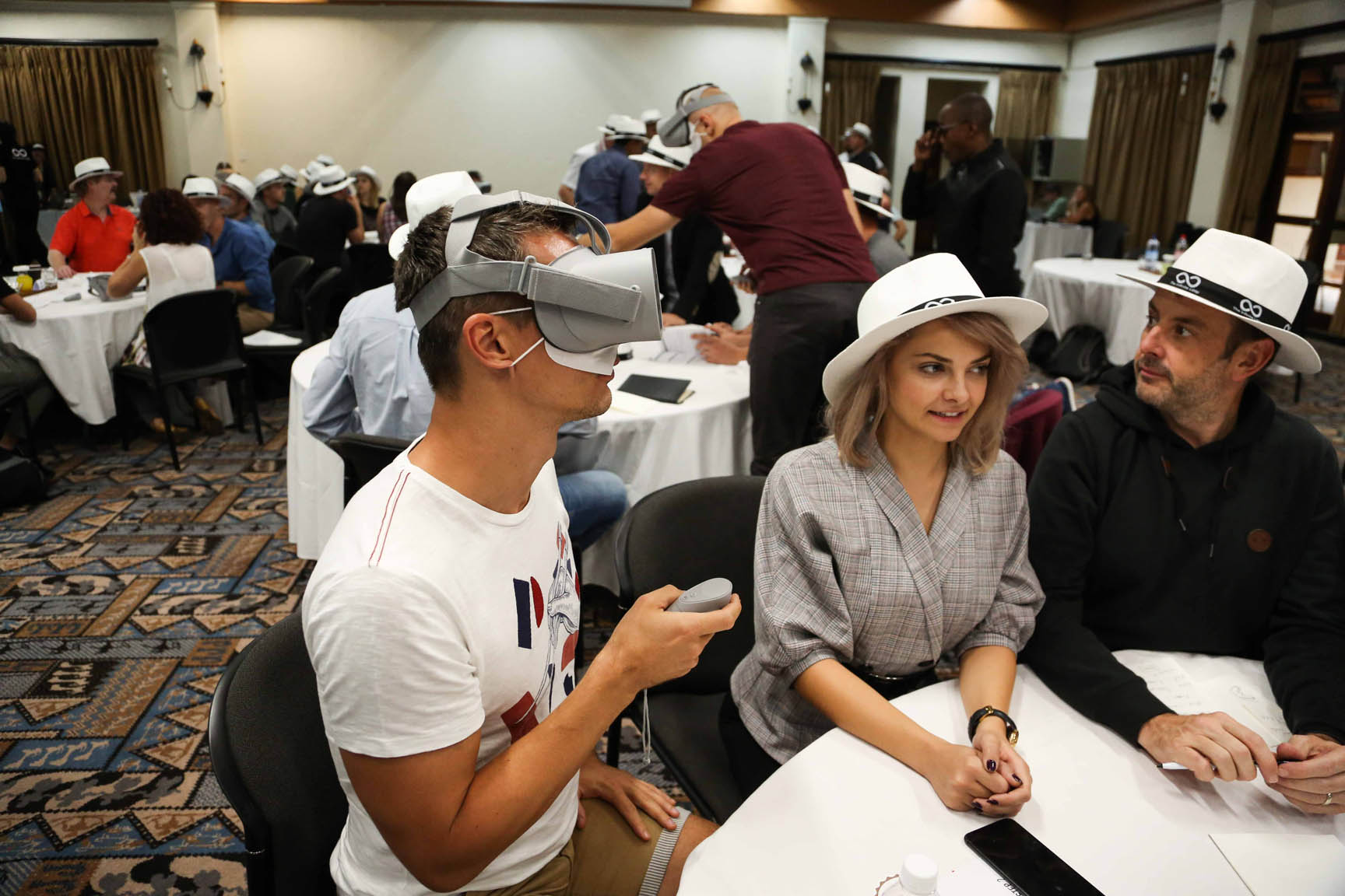 A delegate with a virtual reality headset on, while sitting with his teammates during team building game infinite loop.