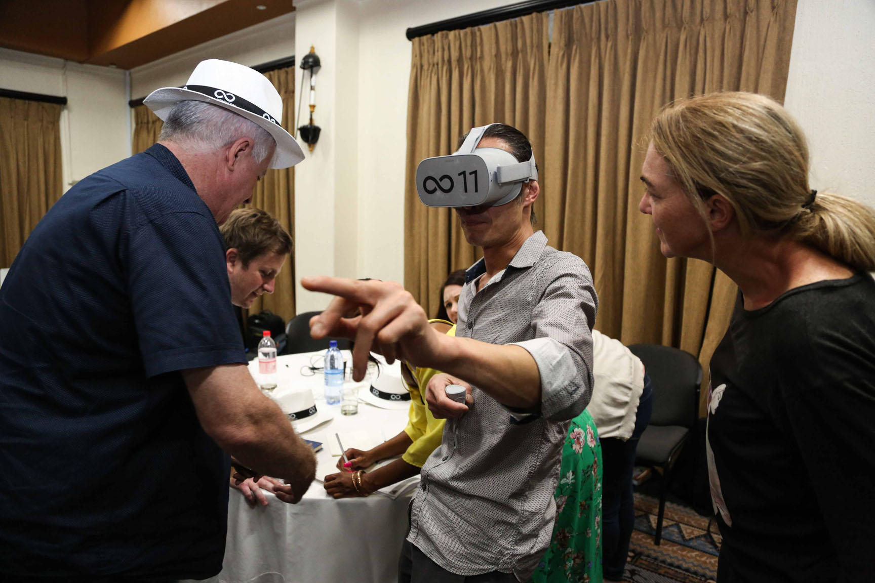 A delegate with a virtual reality headset on, while his teammates give him direction on how to proceed with the VR game.