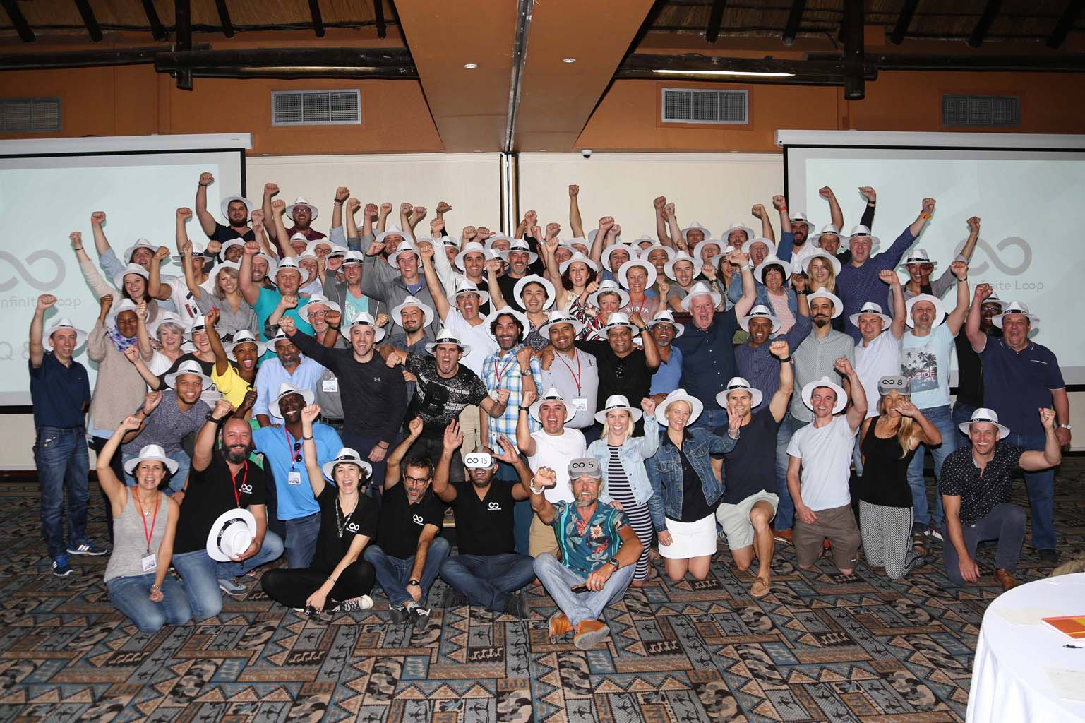 A large group of delegates smiling for a photo during their virtual reality team building challenge with Orangeworks.