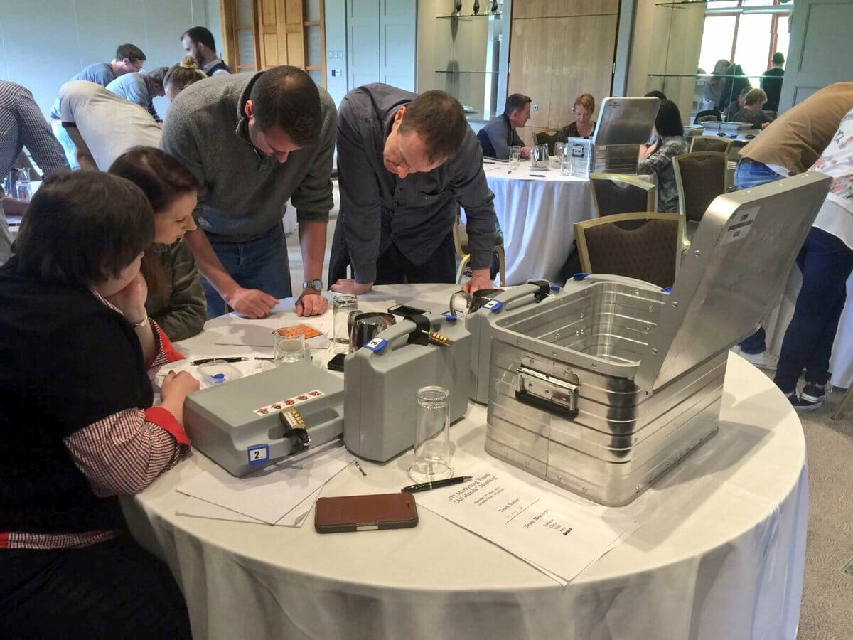 Delegates solving puzzles during their beat the box team building activity.