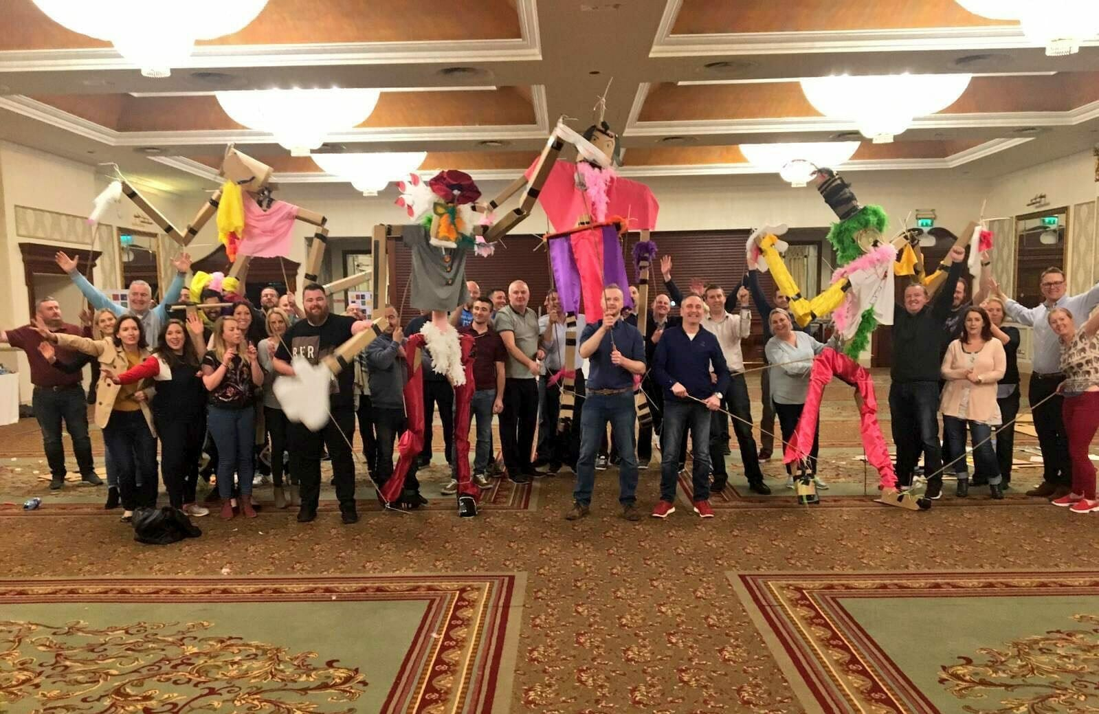 Delegates holding up the giant puppets they created during their teambuilding day with Orangeworks.