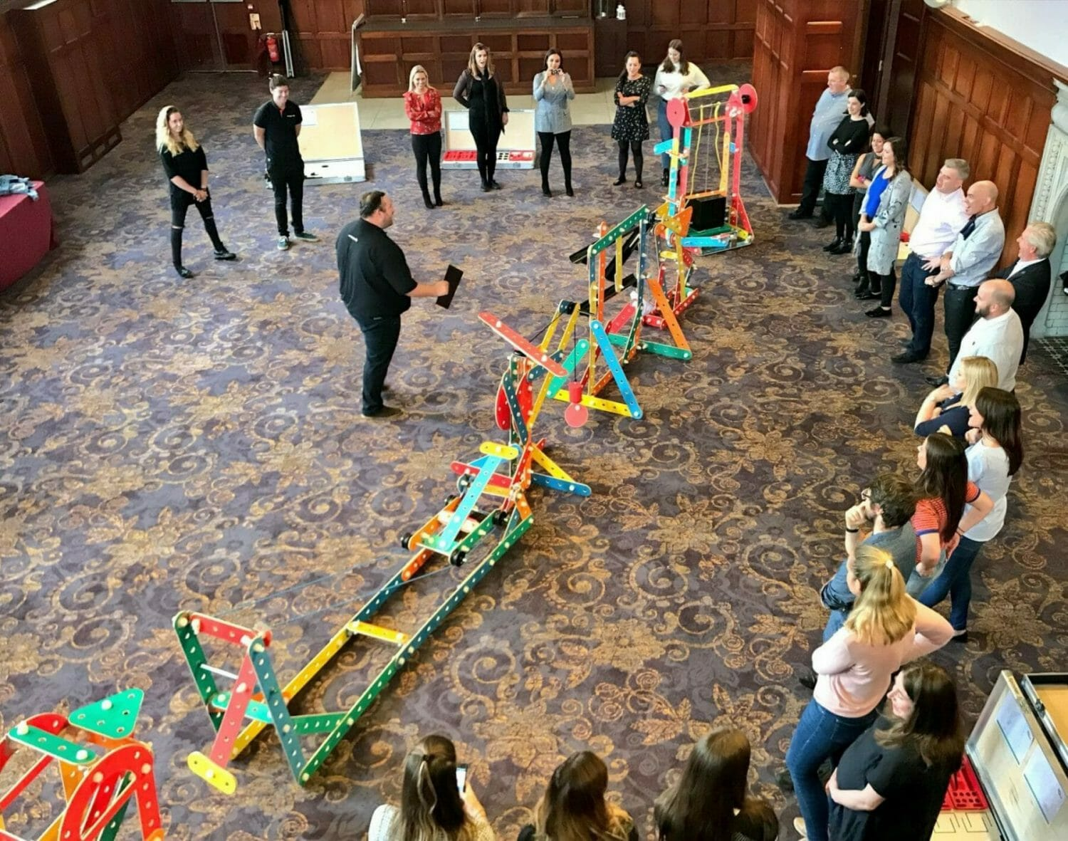 Orangeworks MC Oddie, showing a group of delegates how the team building game Rat Trap works.