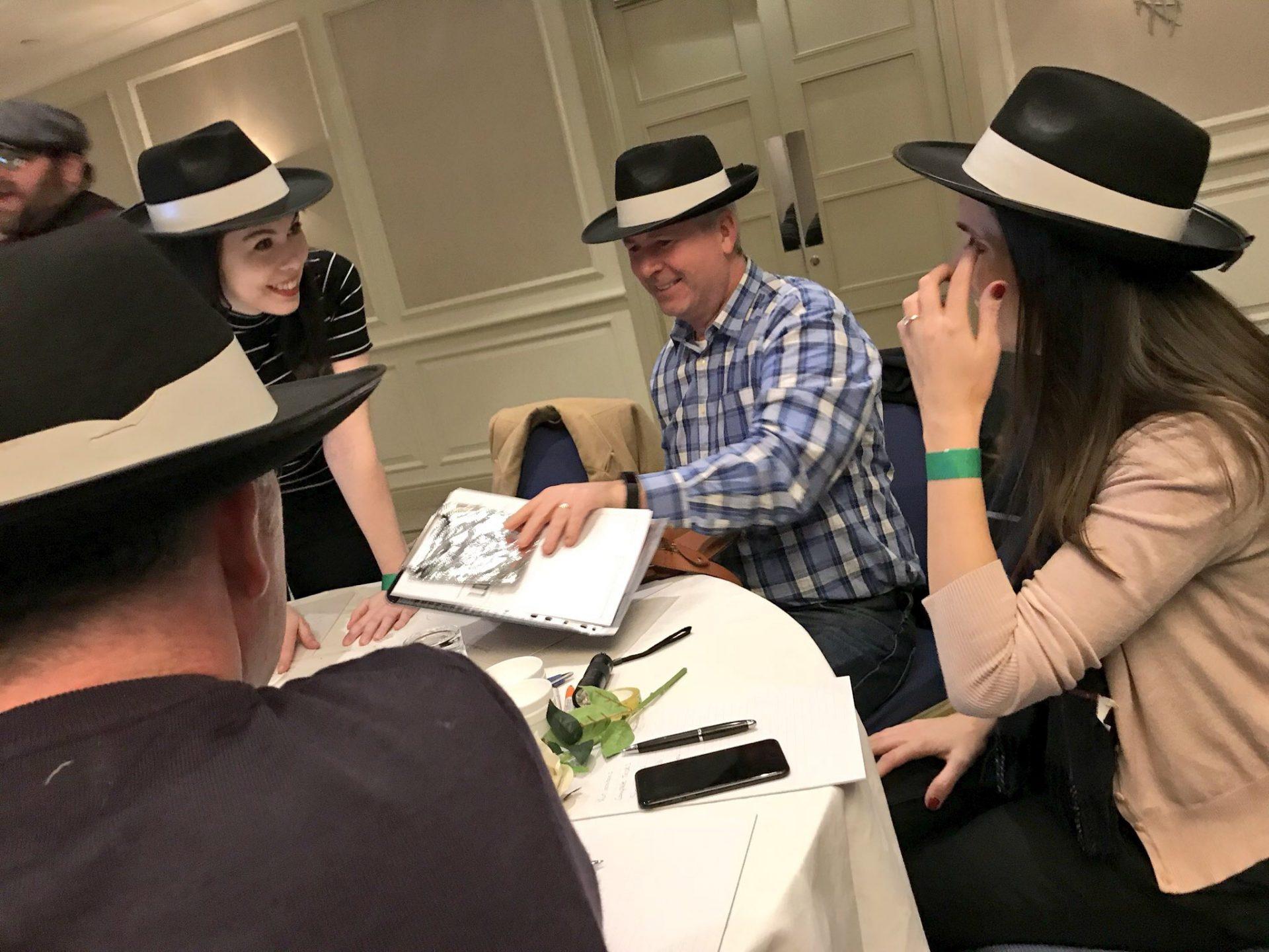 Teams wearing mob hats during their team bonding game with orangeworks.