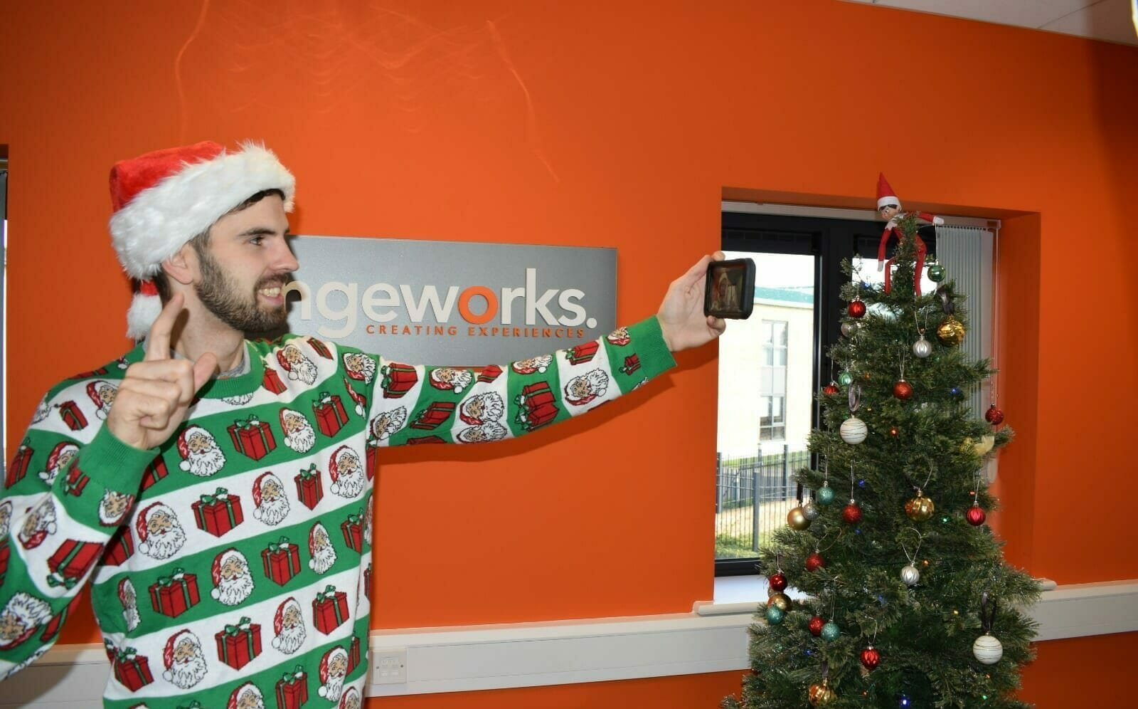 Delegate taking a selfie in front of the Orangeworks sign as part of one of their Christmas online games for remote teams.