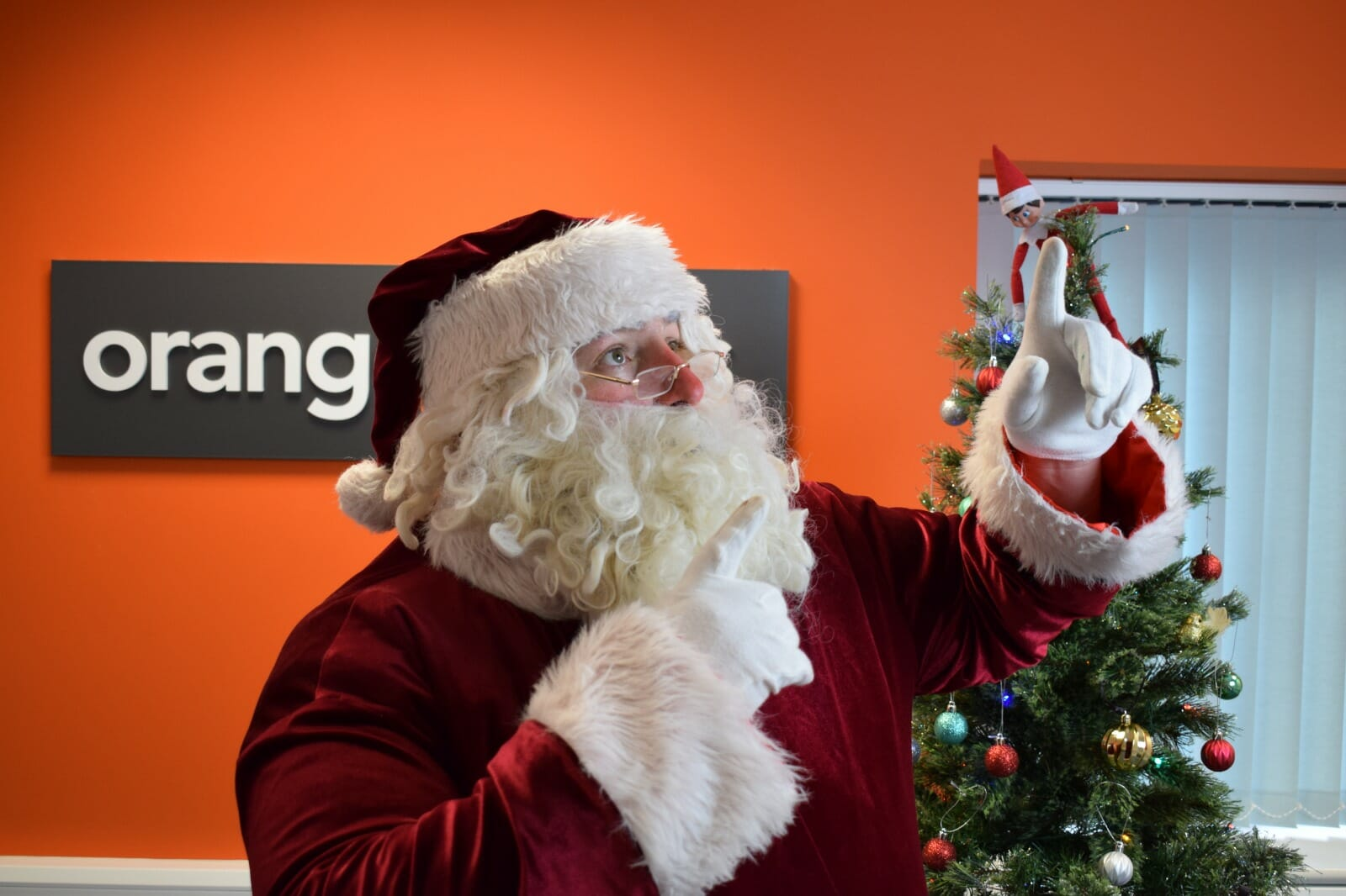 Santa pointing to the sky as he plays Orangeworks virtual work Christmas party game called Who Stole Santa.