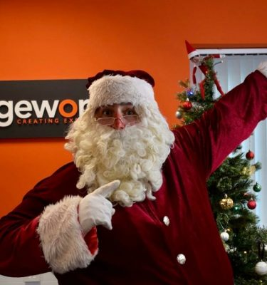 Santa pointing up to the left while standing in front of a Christmas tree and the Orangeworks logo.