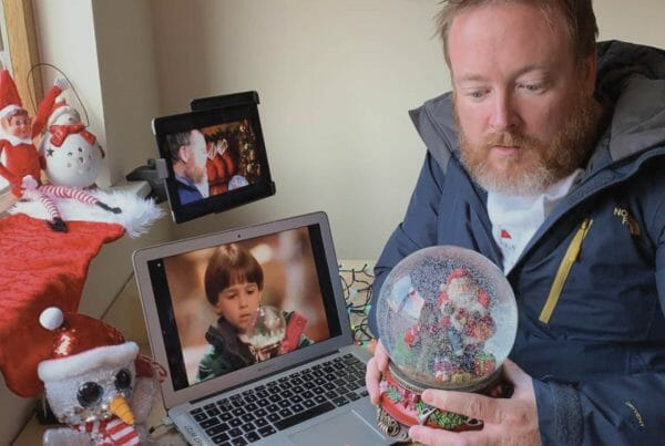 Delegate looking at a snowglobe as he plays Orangeworks virtual work Christmas party game called A Picture Perfect Christmas
