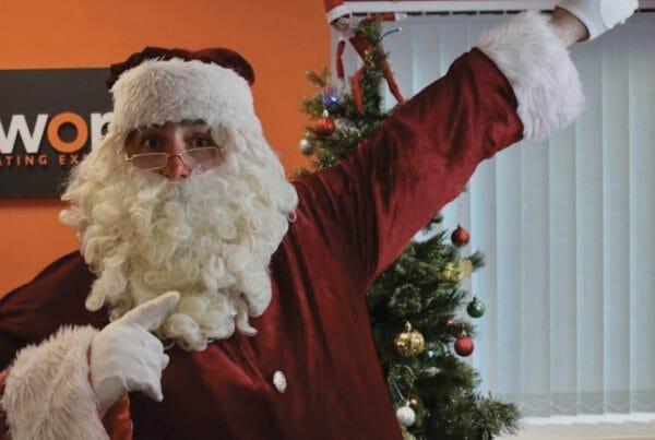 Oddie, Orangeworks MC, dressed as Santa, ready to start playing Who Stole Santa? a festive remote team building activity.